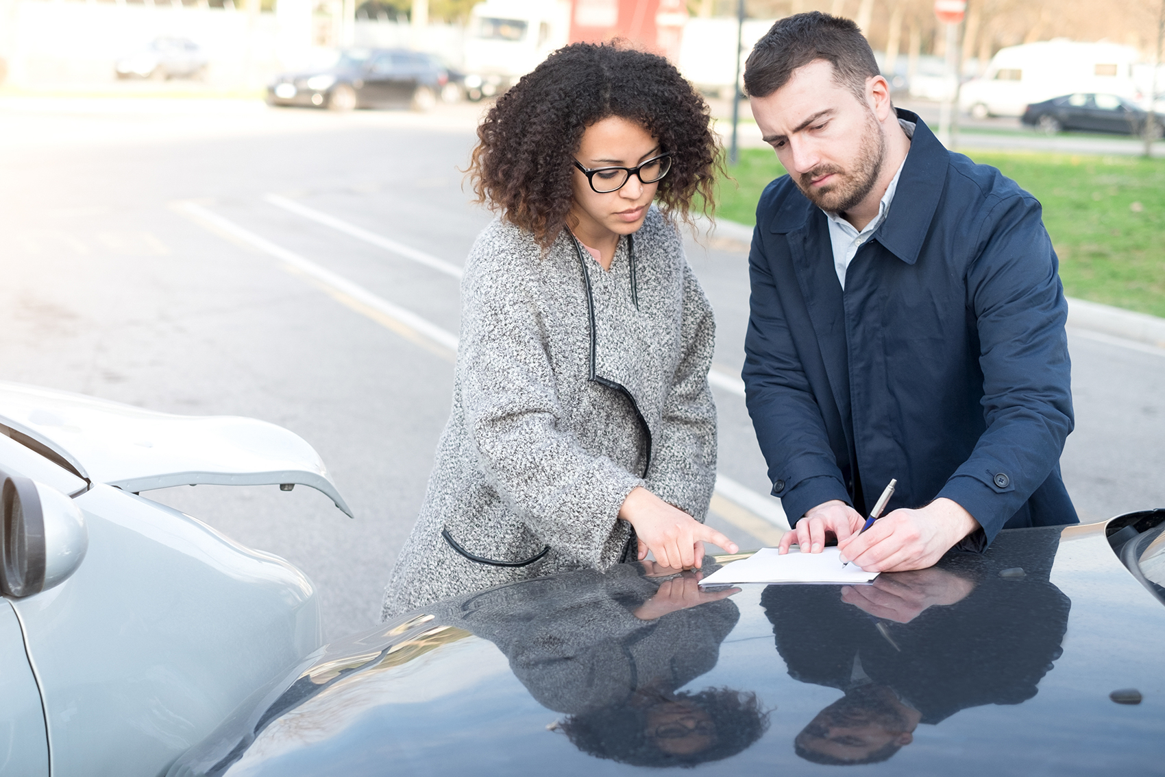 Man and woman exchanging insurance in front of car