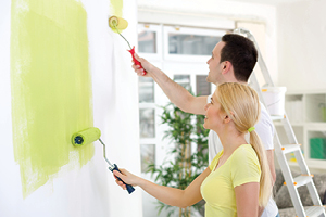 Young couple painting wall within home