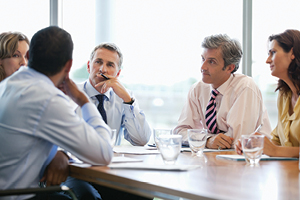 Business meeting with women and men business professional sitting at a table