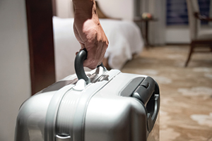 Close-up of person's hand holding suitcase.