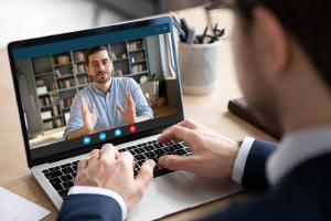 Businessman at computer attending virtual meeting