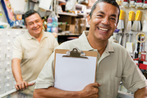 man holding clipboard in hardware store with another man in background behind a desk