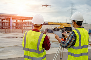 two construction workers operating a drone on site