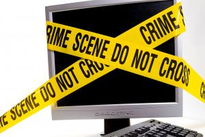 "A desktop computer with a monitor wrapped in ""crime scene"" tape."