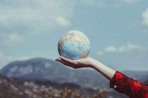 A hand holds a globe outdoors in front of a mountainous backdrop.