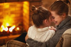 Image of mother and daughter snuggled up by a fireplace
