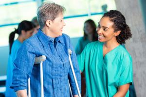 Healthcare professional safely helping woman on crutches during physical therapy session.