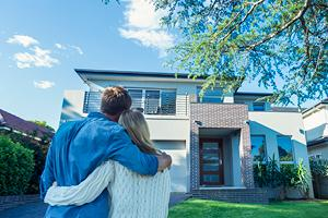 Couple standing and hugging in front of home