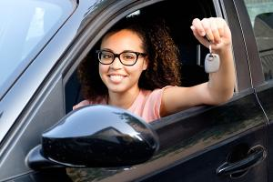 happy young woman seated in car holding car keys
