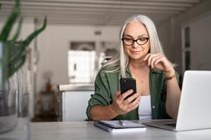 Woman at laptop looking at phone