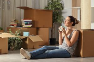smiling woman sitting with moving boxes drinking a cup of coffee