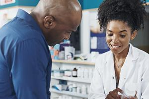 pharmacist showing prescription to customer