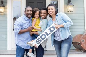 family outside new home holding sold sign