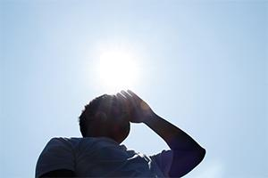 A person blocking the sun on a hot day