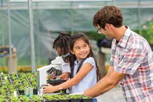 Student smiling at teacher in greenhouse