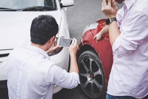 person taking digital photos at a car accident