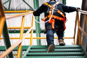 man with fall protection walking up stairs