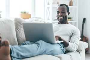 Young man looking at laptop and smiling while lying on the sofa at home