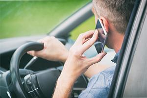 Man driving a car while talking on mobile phone