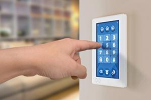wall display showing house alarm security system with secret code number keypad with sensors and lock status. Hands pointing at touch display, digiting secret code number.